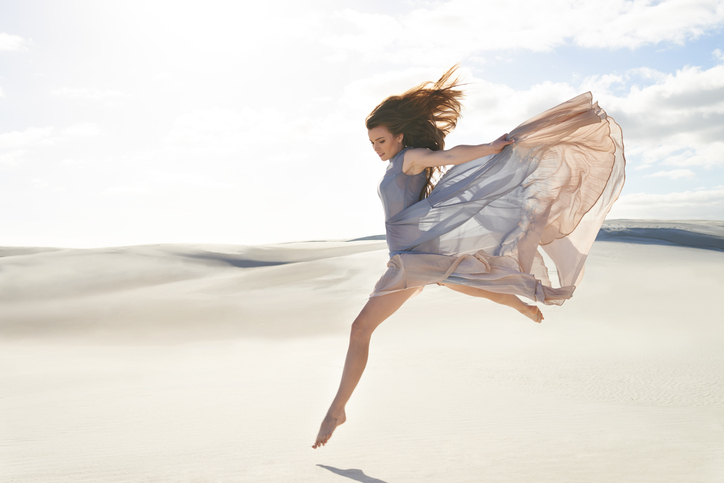 Side view of a beautiful young woman in a flowing dress jumping across sandhttp://195.154.178.81/DATA/i_collage/pi/shoots/783224.jpg